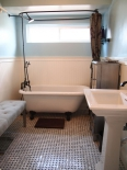 Bathroom with claw foot tub and marble tile floor